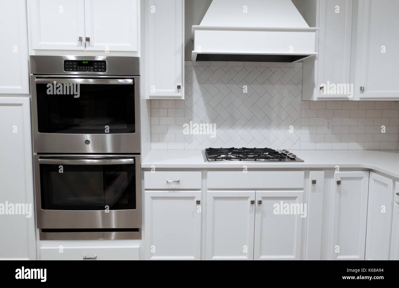 Una cucina bianca con parete in acciaio inossidabile forni un