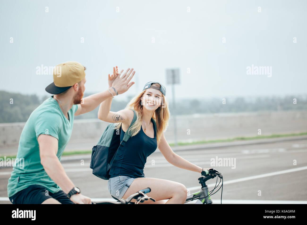 Montare il ciclista giovane permanente al vertice fiving elevata in una giornata di sole Foto Stock