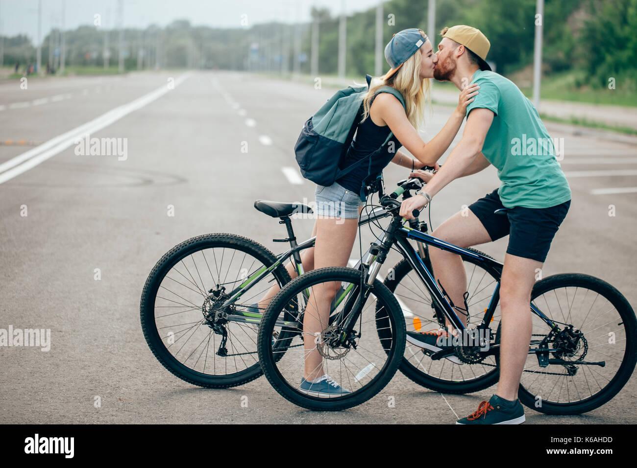 Bella giovane coppia ama camminare con le biciclette, baciare e avvolgente. Stare vicino alla bici. Il concetto di riposo attivo Immagini Stock