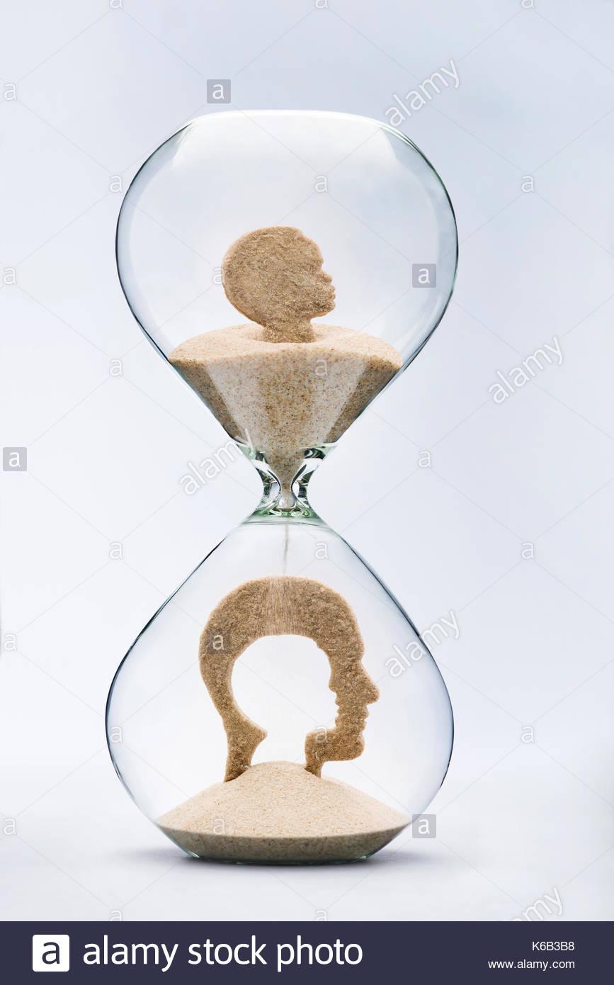 Infanzia nostalgia concetto con la caduta di sabbia prendendo la forma di tagliare la testa del bambino all'interno di una testa di uomo, all'interno di una clessidra Immagini Stock
