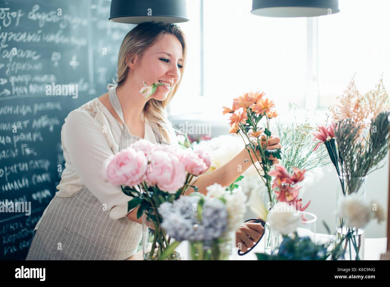 Sorridente bella giovane donna fioraio disponendo le piante nel negozio di fiori Immagini Stock