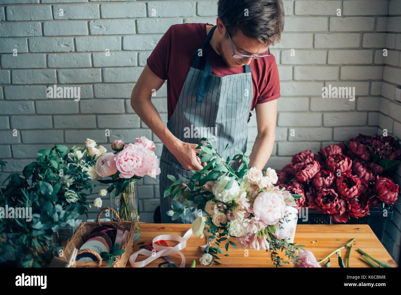 Giovane maschio fioraio funzionante a contatore nel negozio di fiori Immagini Stock