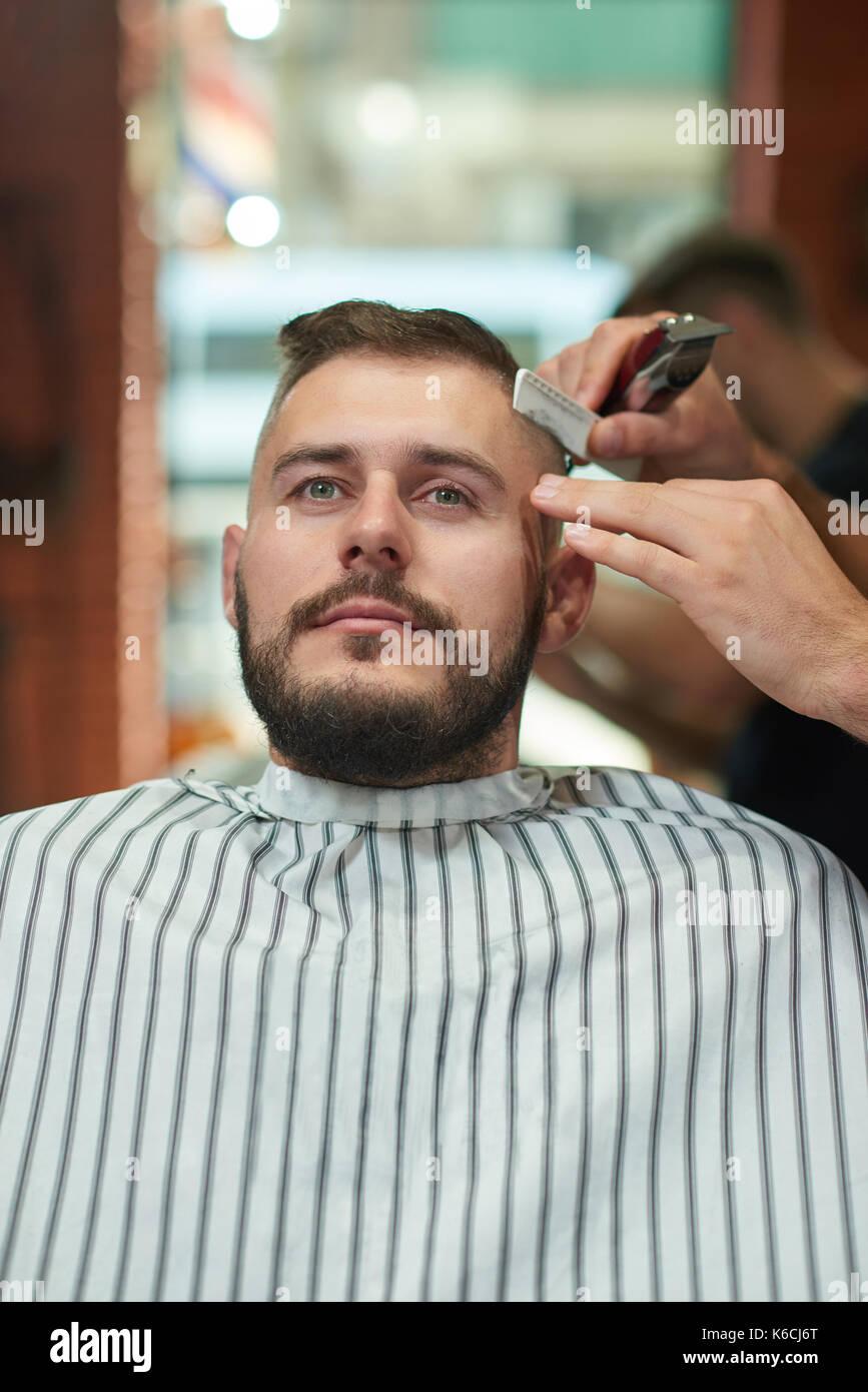 Giovane uomo al barbiere Immagini Stock