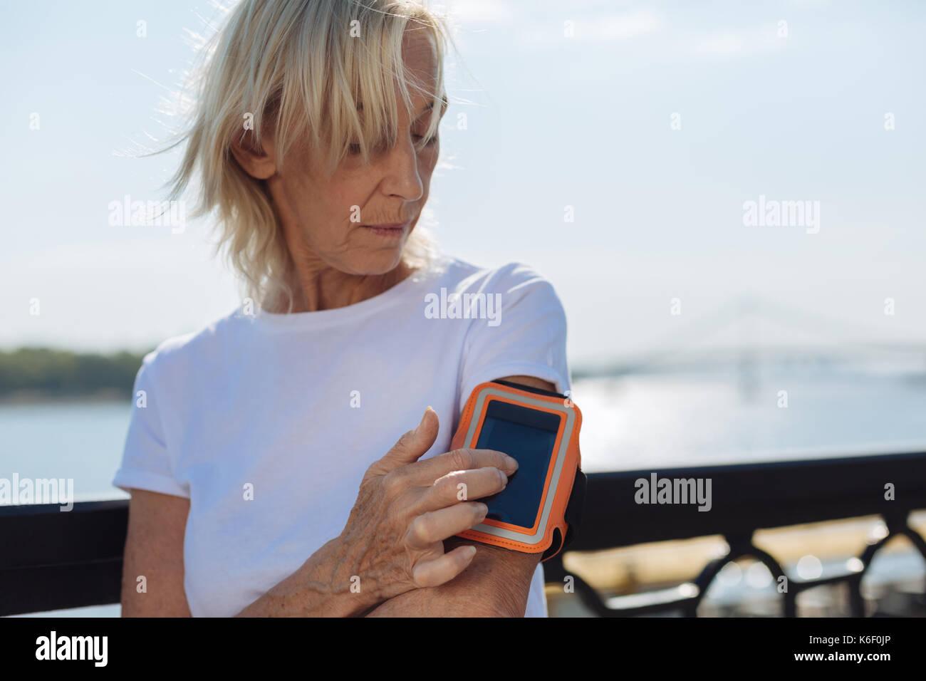 Athletic anziana signora distanze di rilevamento con il telefono in fascia per il braccio Immagini Stock