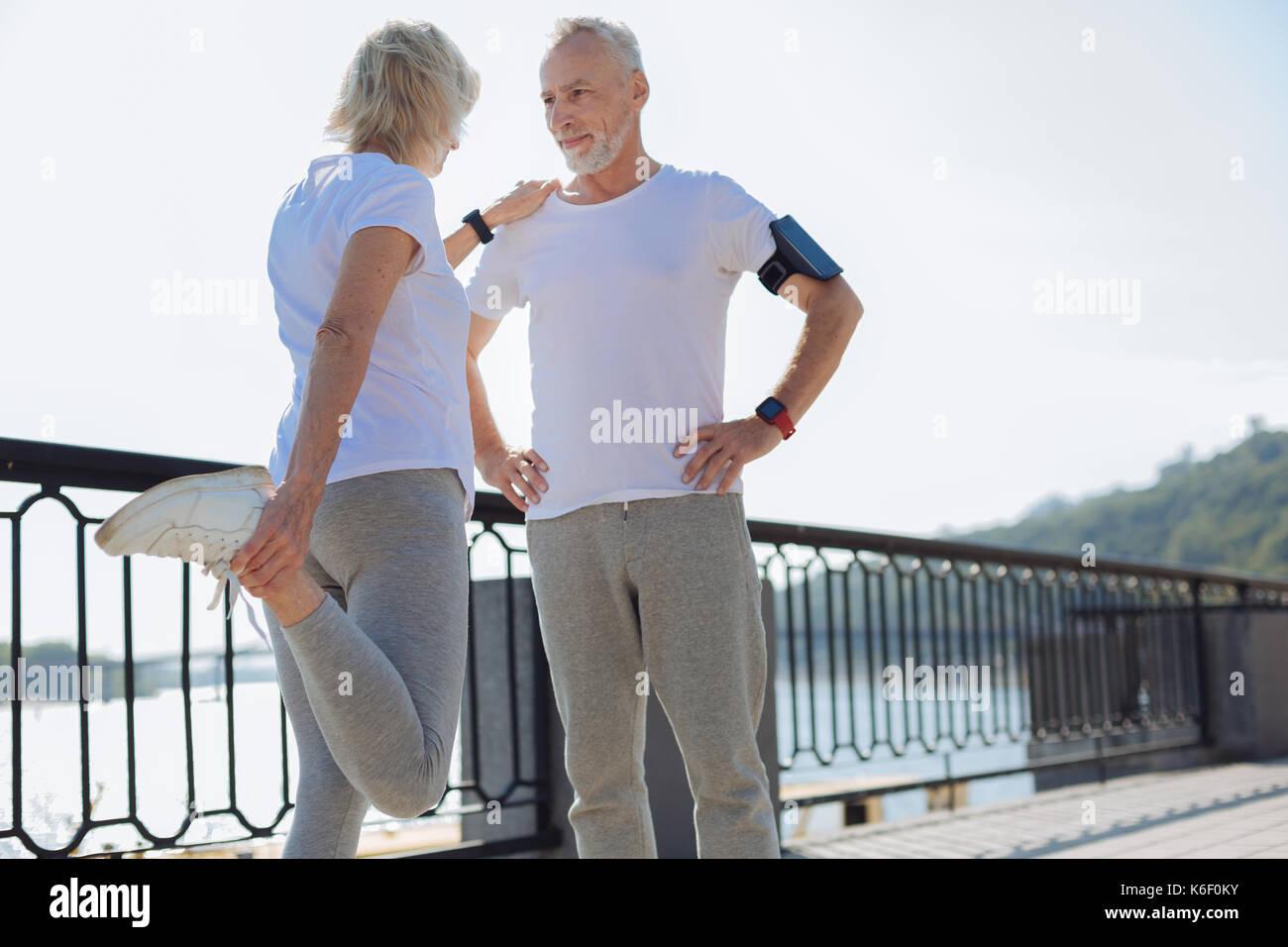 Montare la donna appoggiata sul marito durante lo stiramento Immagini Stock