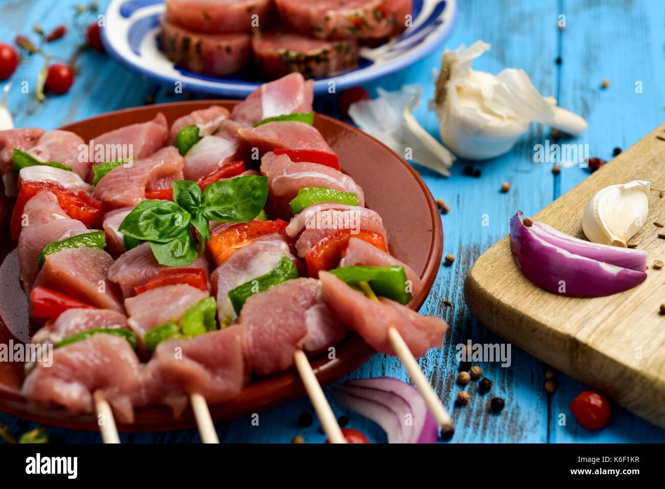 Primo piano di alcune materie di carne di tacchino Spiedini misti con verdure in un piatto di terracotta, posto su un blu tavola in legno rustico Immagini Stock