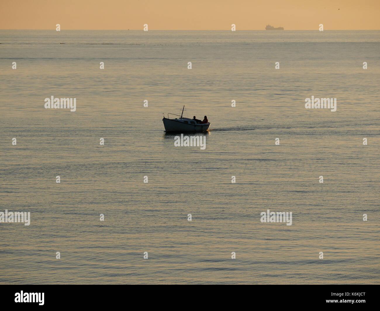 Tramonto a Hönö, Klåva, nell'arcipelago di Goteborg. Barca con due persone al passaggio, nave di trasporto in background. Foto Stock