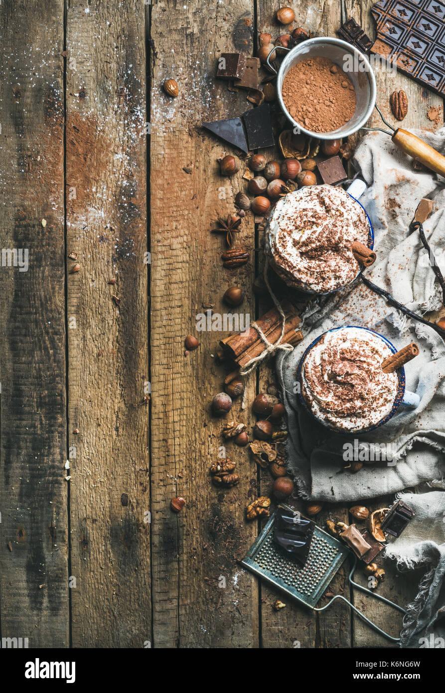 Cioccolata calda con panna montata, noci, spezie e cacao in polvere Immagini Stock