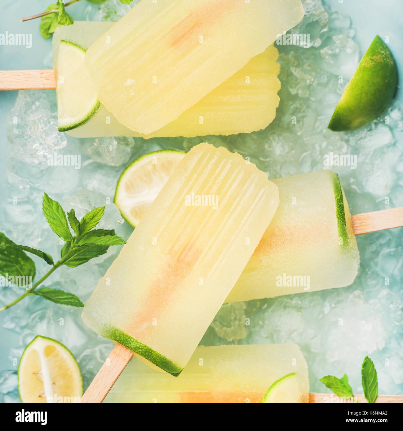 Estate rinfrescante limonata popsicles con lime e menta con scaglie di ghiaccio su sfondo blu, vista dall'alto, quadrato ritaglia Immagini Stock