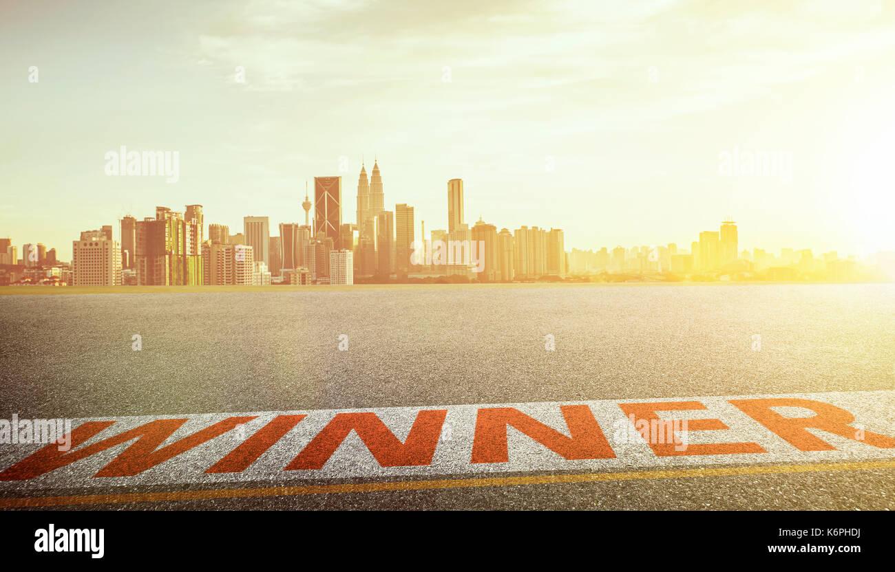 Vista del vuoto strada asfaltata al vincitore la parola e dello skyline della città sfondo . sera scena . Foto Stock