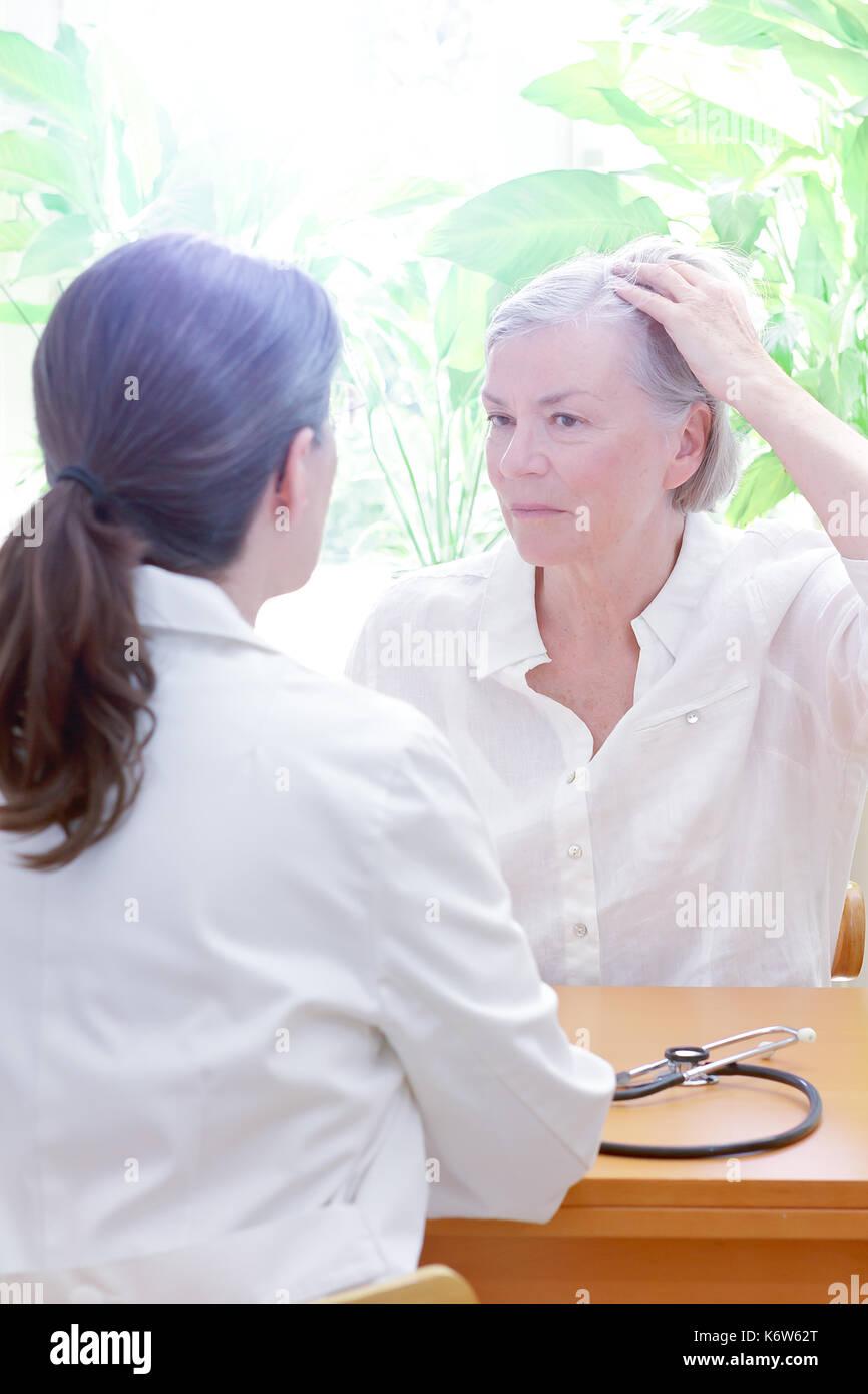 Senior donna mostrando il suo assottigliamento dei capelli o alopecia al suo medico donna o il medico, spazio di copia Immagini Stock
