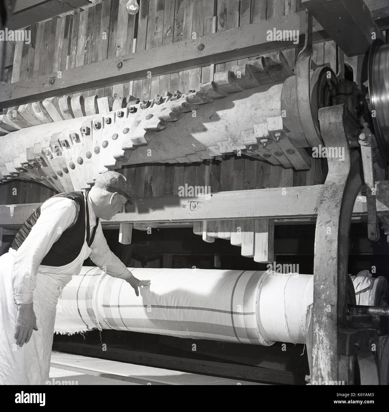 Degli anni Cinquanta, Irlanda del Nord, maschio operaio tessile di controllare la qualità del finito di tela di lino strettamente avvolta sul gigante rotoli di legno di Belfast. Immagini Stock