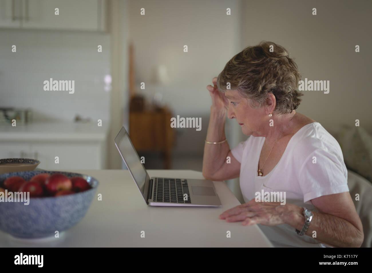 Tense senior donna utilizzando laptop in cucina a casa Immagini Stock