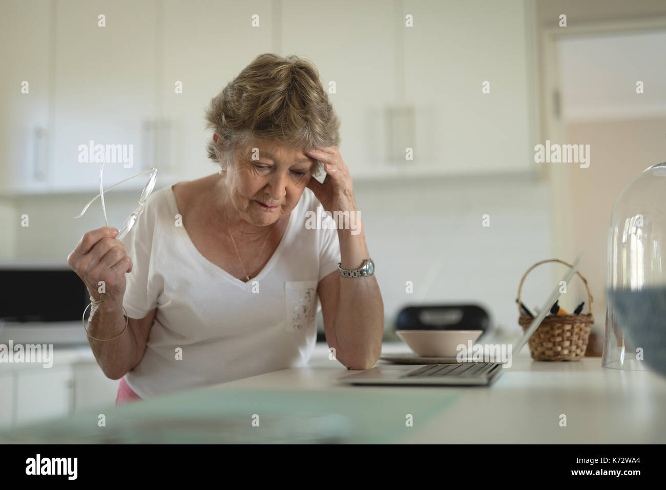 Tense senior woman standing in cucina con computer portatile sul piano di lavoro a casa Immagini Stock