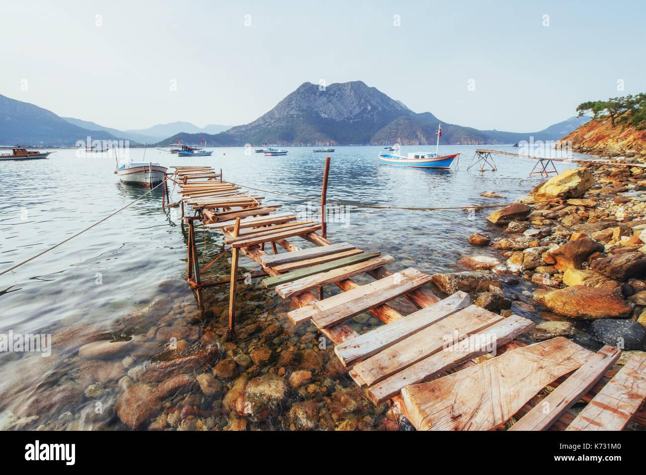 Barche vicino al molo rotto, mettendo in una quiete serena blu acqua di mare Immagini Stock