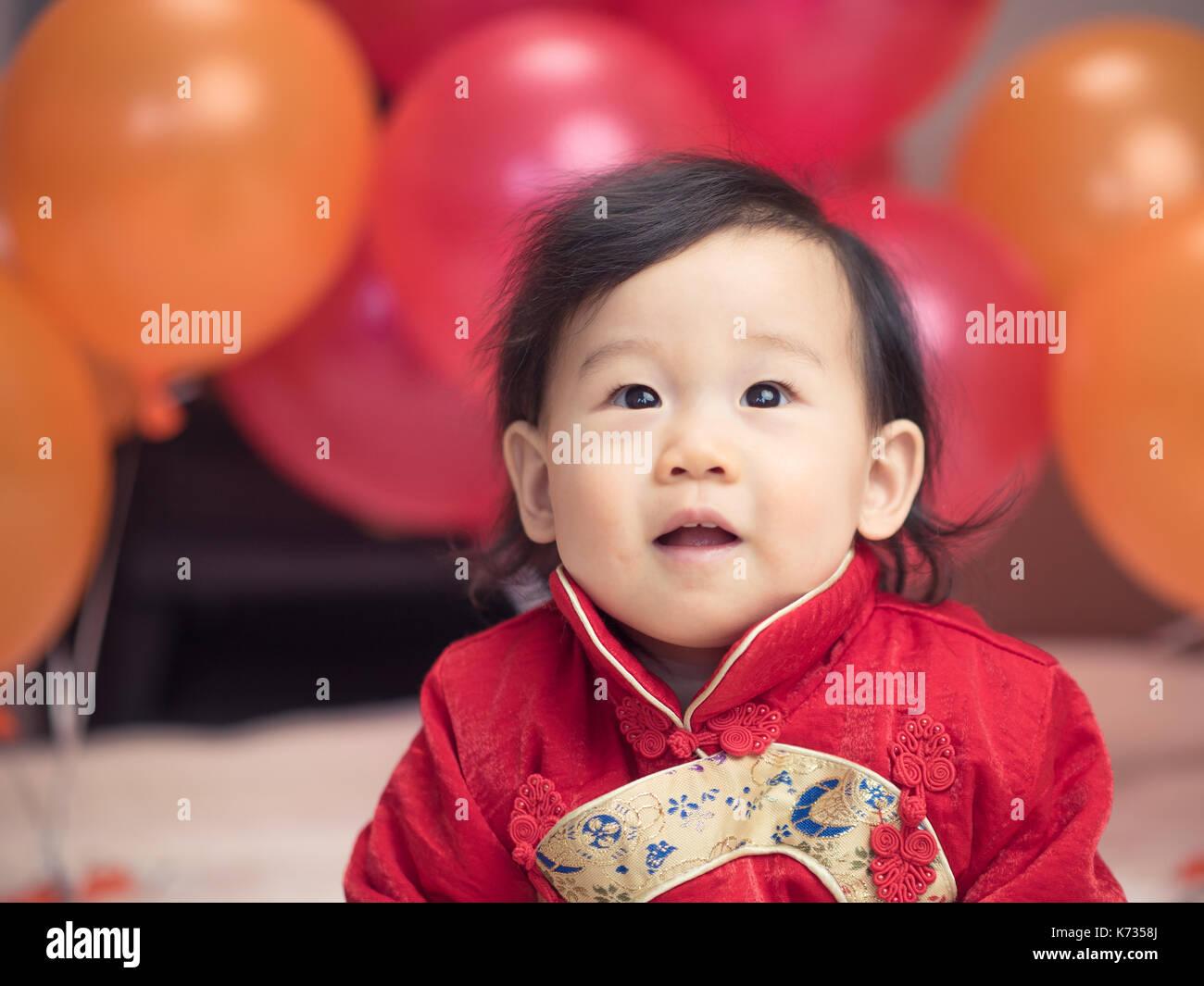 Carino asian bambina con le medicazioni tradizionali per il suo primo compleanno Immagini Stock