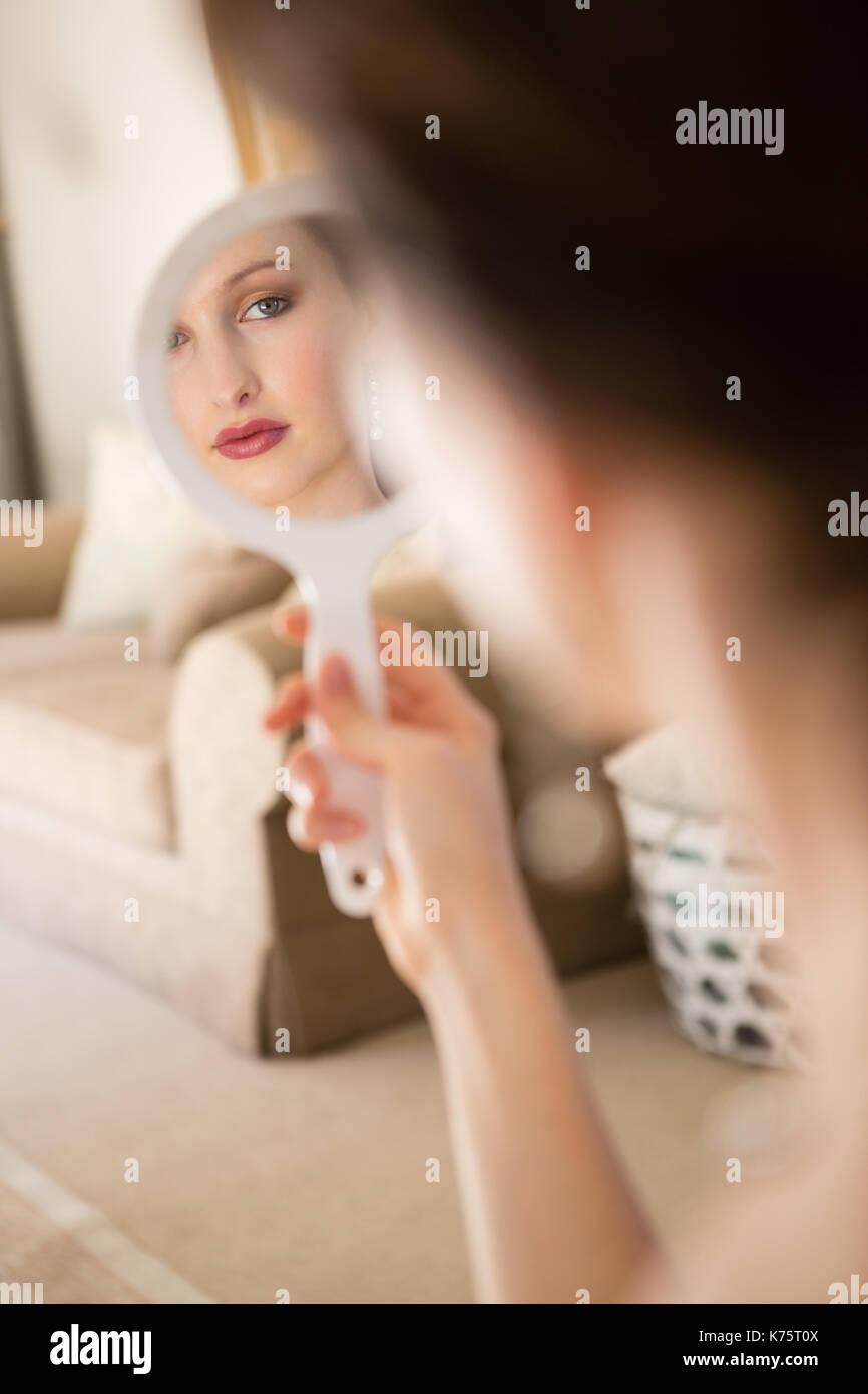 Bella sposa guardando nello specchio a mano a casa Foto Stock
