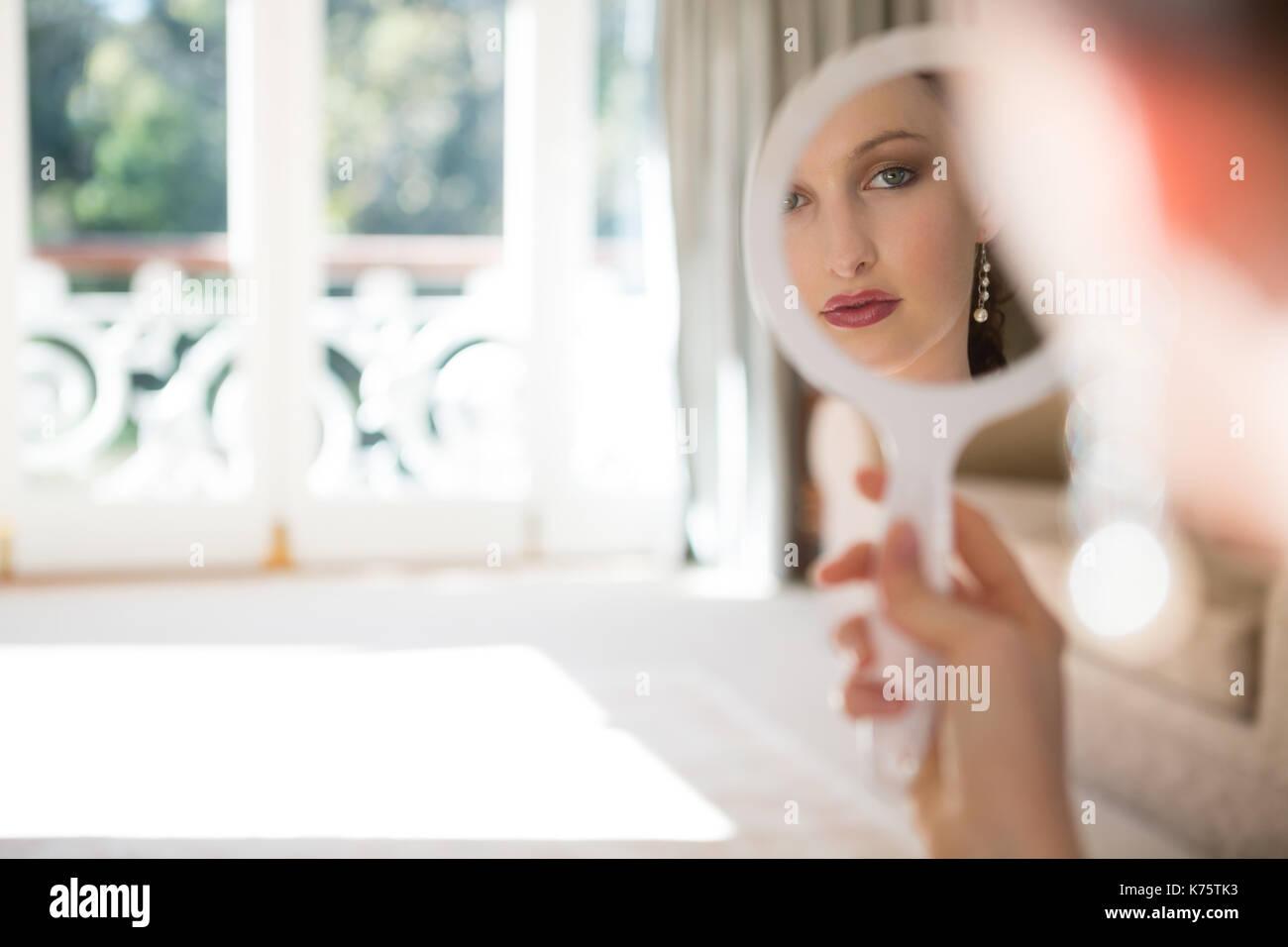 Bella sposa guardando nello specchio a mano a casa Immagini Stock