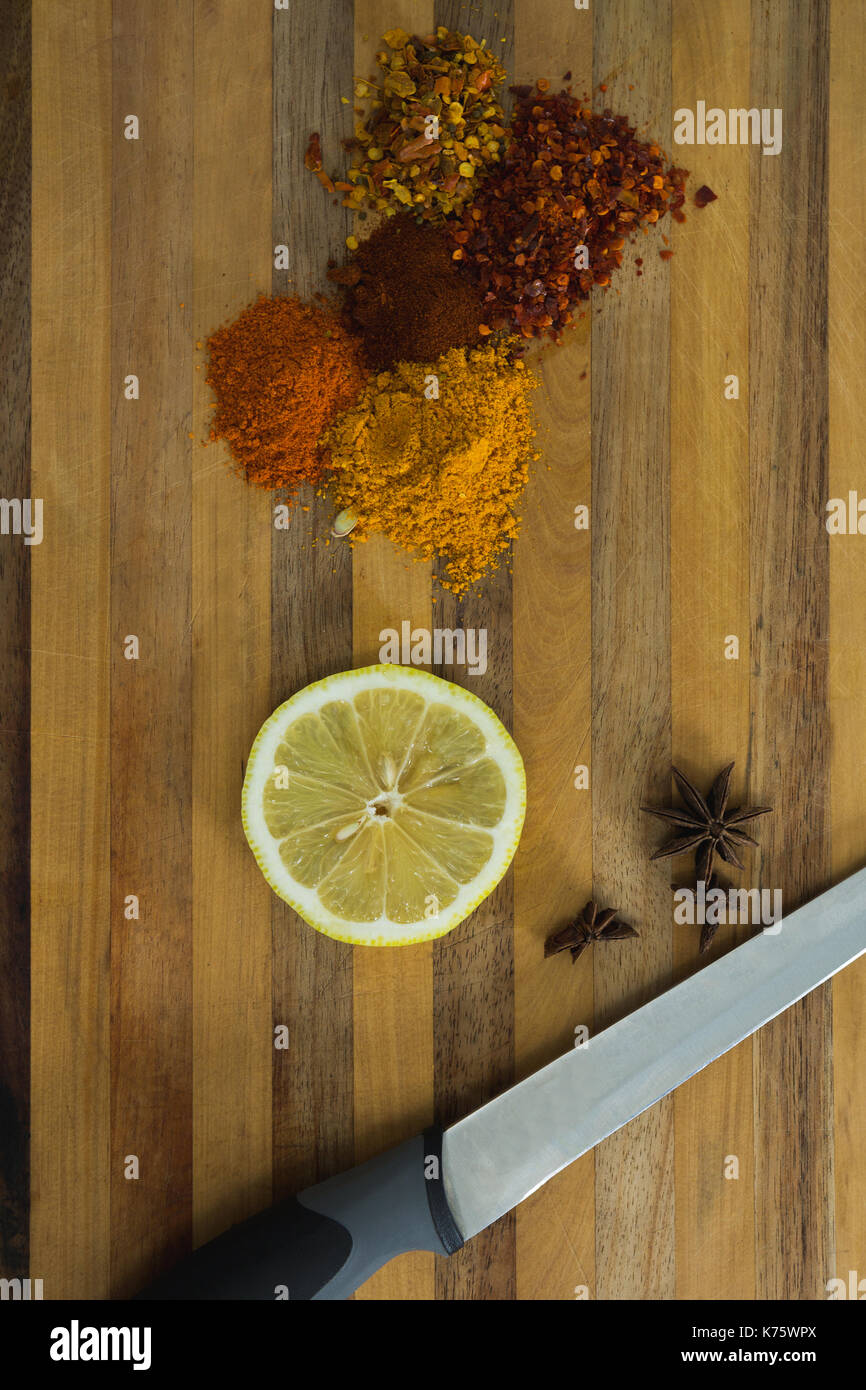 Sovraccarico di varie spezie con fettina di limone e un coltello sul tagliere Immagini Stock
