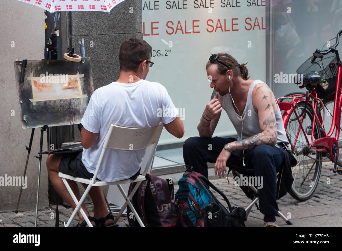 2 gli uomini a parlare di una pittura presso la strada di copenhagen. Immagini Stock