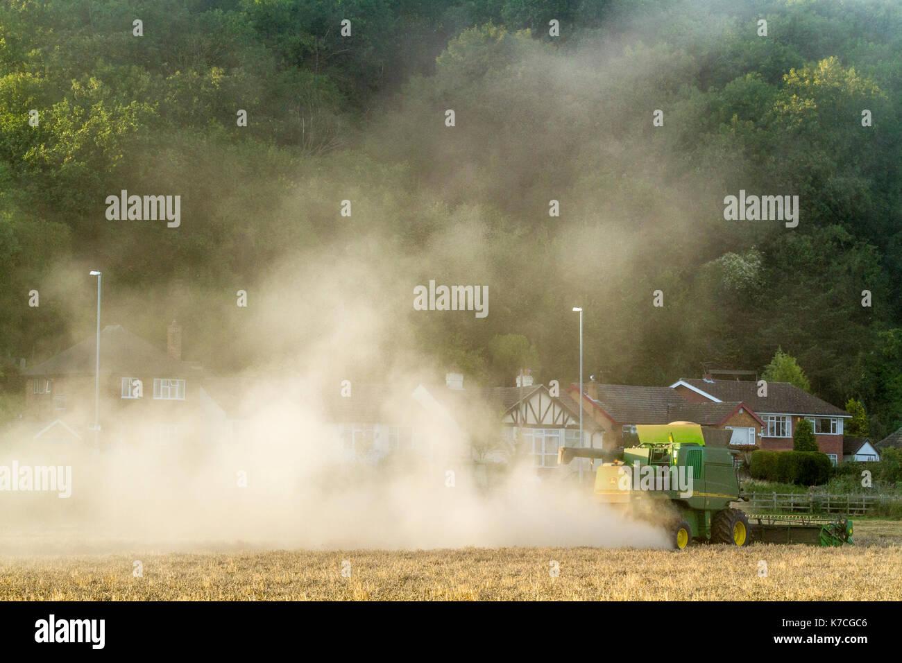 Rurale di problemi ambientali. Inquinamento atmosferico in campagna. Macchina mietitrebbiatrice causando il frumento polvere di grano nei pressi di alloggiamento, Nottinghamshire, England, Regno Unito Foto Stock