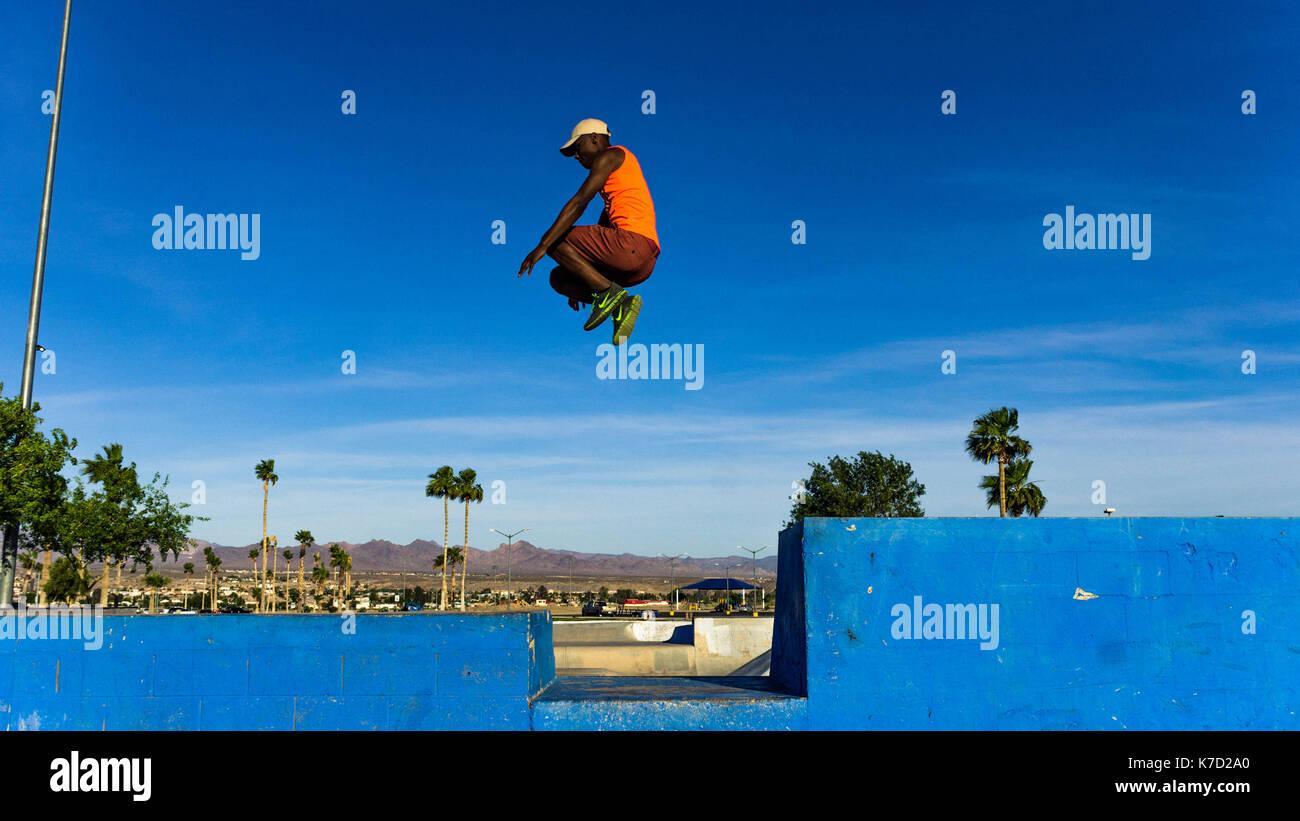 Parkour salto a un parco locale attraverso alcune rampe di skateboard. Immagini Stock