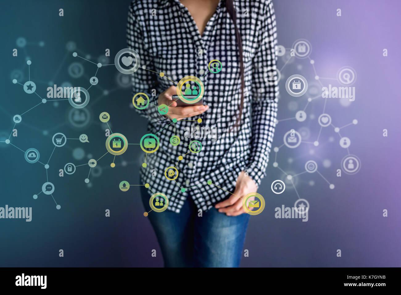La tecnologia di comunicazione sulla vita quotidiana tramite smart phone concetto, social media o sistema di rete presente su blured hipster femmina e permanente enjoyin Immagini Stock