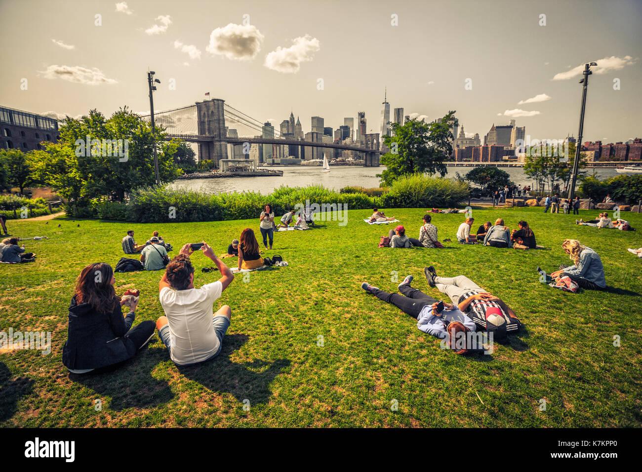 Per coloro che godono di tempo libero in vista del Ponte di Brooklyn e Manhattan dal lato Brooklyn Immagini Stock
