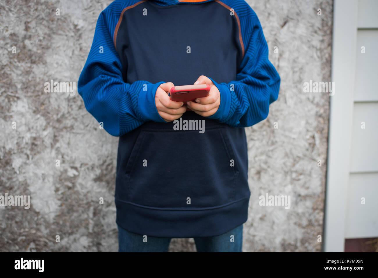 Un giovane ragazzo di testi su un telefono cellulare. Immagini Stock