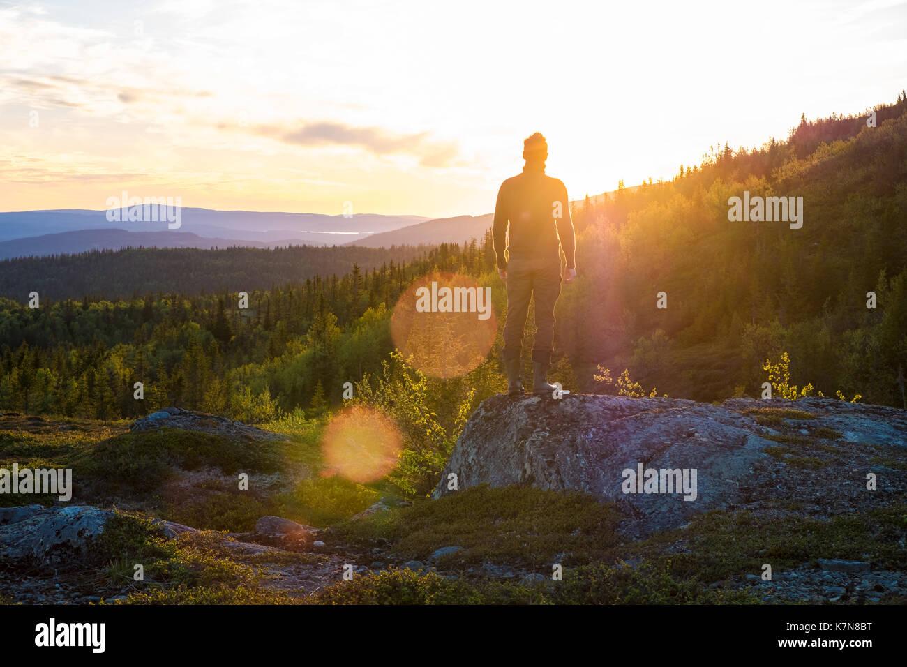 Giovane uomo in piedi sul big stone guardando al tramonto in mezzo al paesaggio Immagini Stock