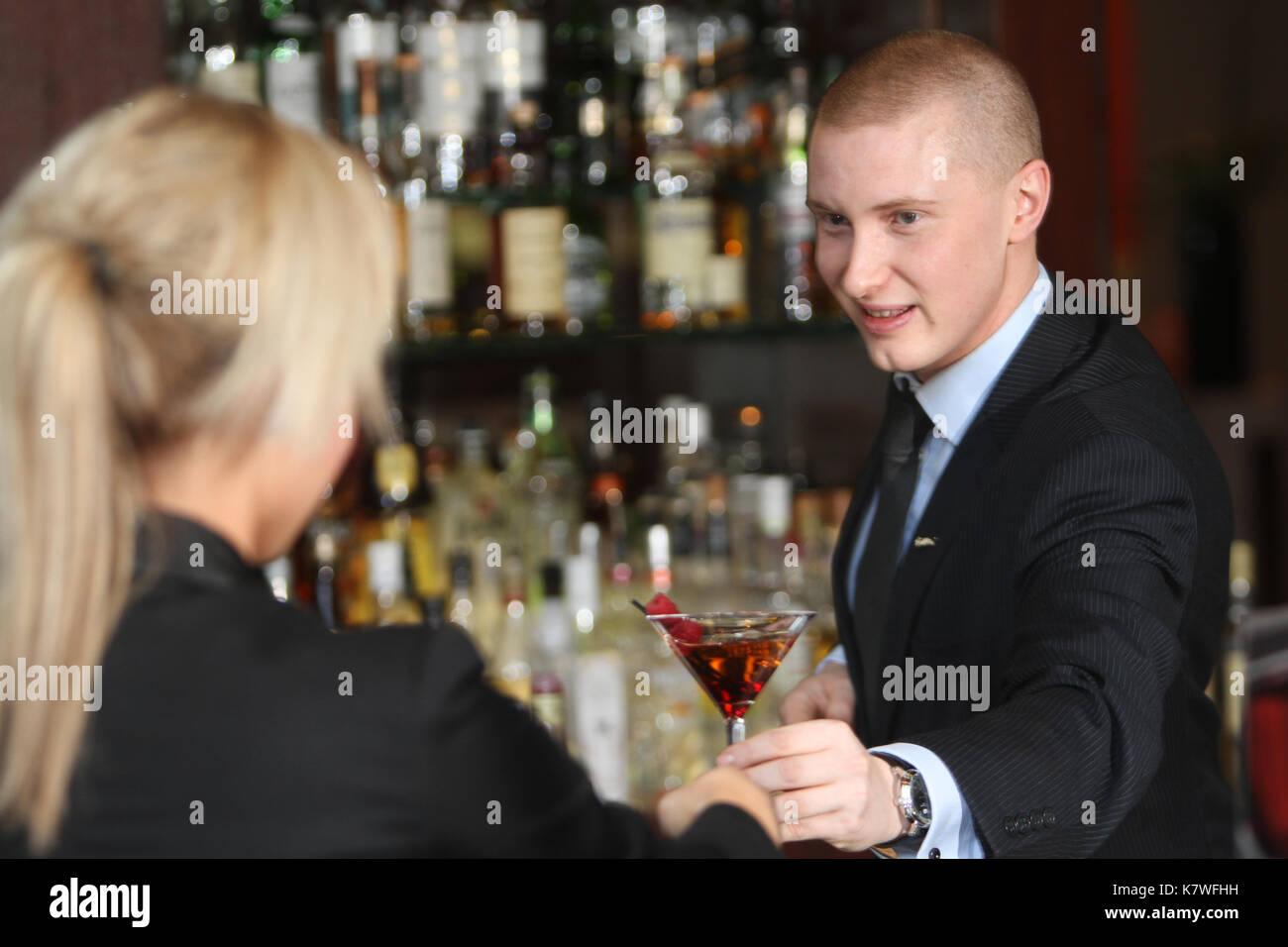 Il barman che serve cocktail al cliente nel bar dell'hotel. Immagini Stock