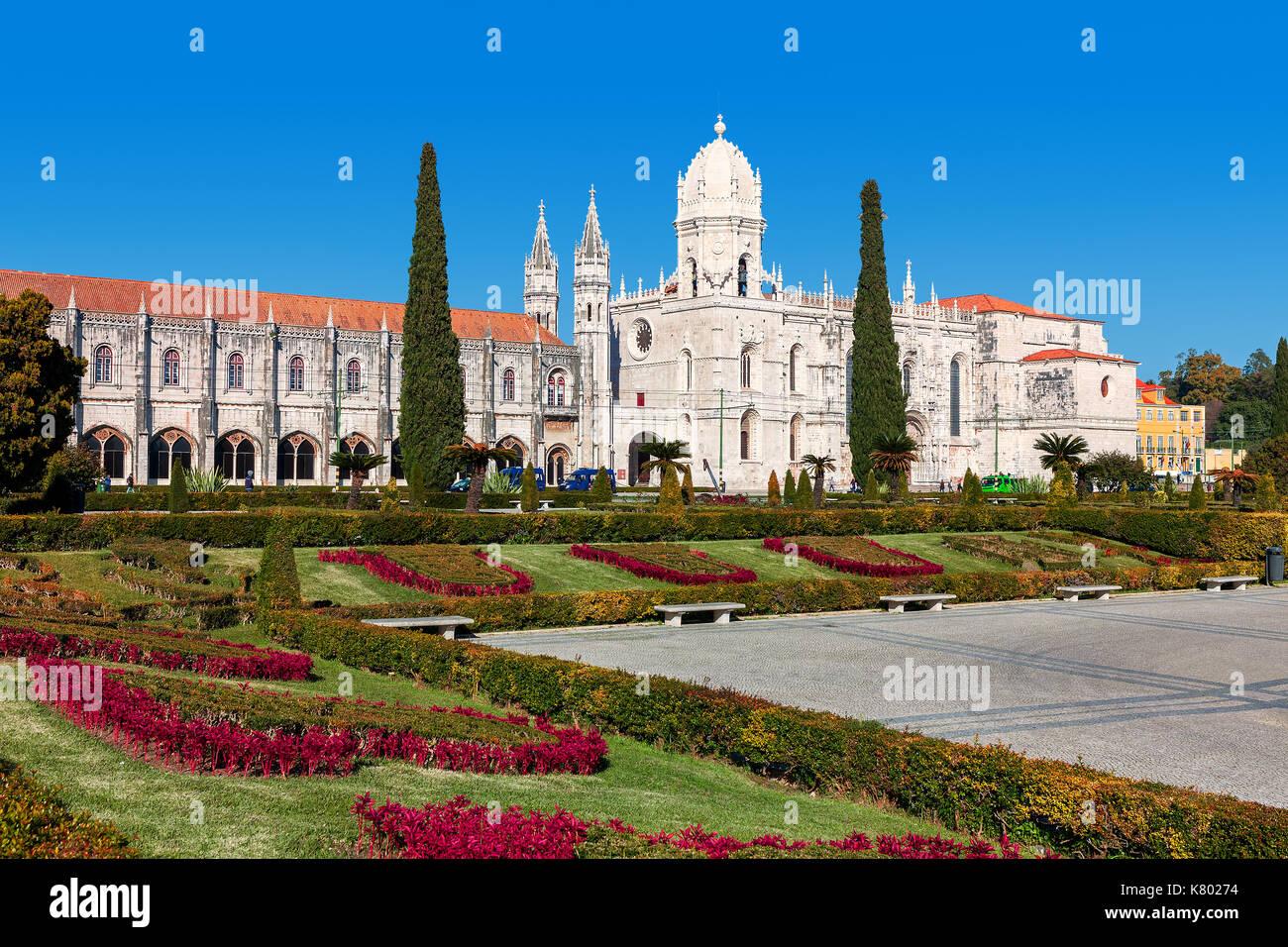 Vista del parco urbano con fiori e jeronimos (aka hieronymites) monastero sotto il cielo blu a Lisbona, Portogallo. Immagini Stock