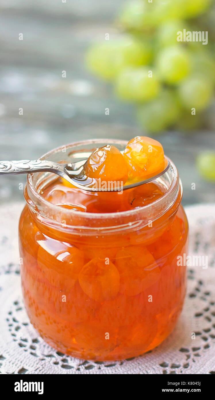 Lo slatko - bianco marmellata di uva (dolce), tradizionale deserto serbo; uve bianche in sciroppo in un vasetto di vetro; vicino, vista verticale Immagini Stock