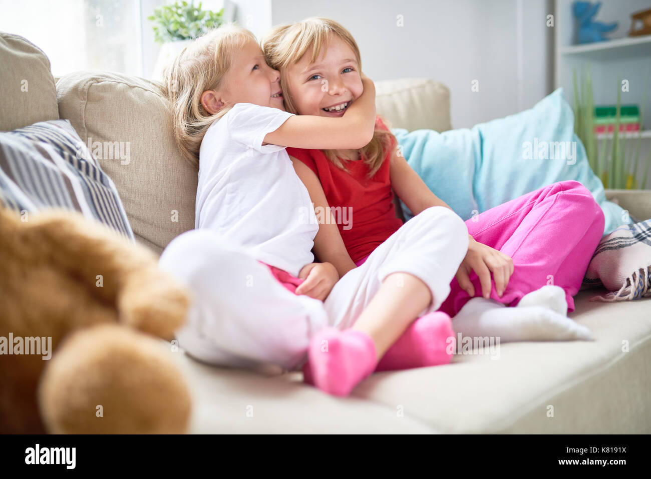 Carino biondo e condivisione ragazza segreto con il suo sorriso sorella maggiore spendendo fine settimana insieme a accogliente soggiorno Immagini Stock