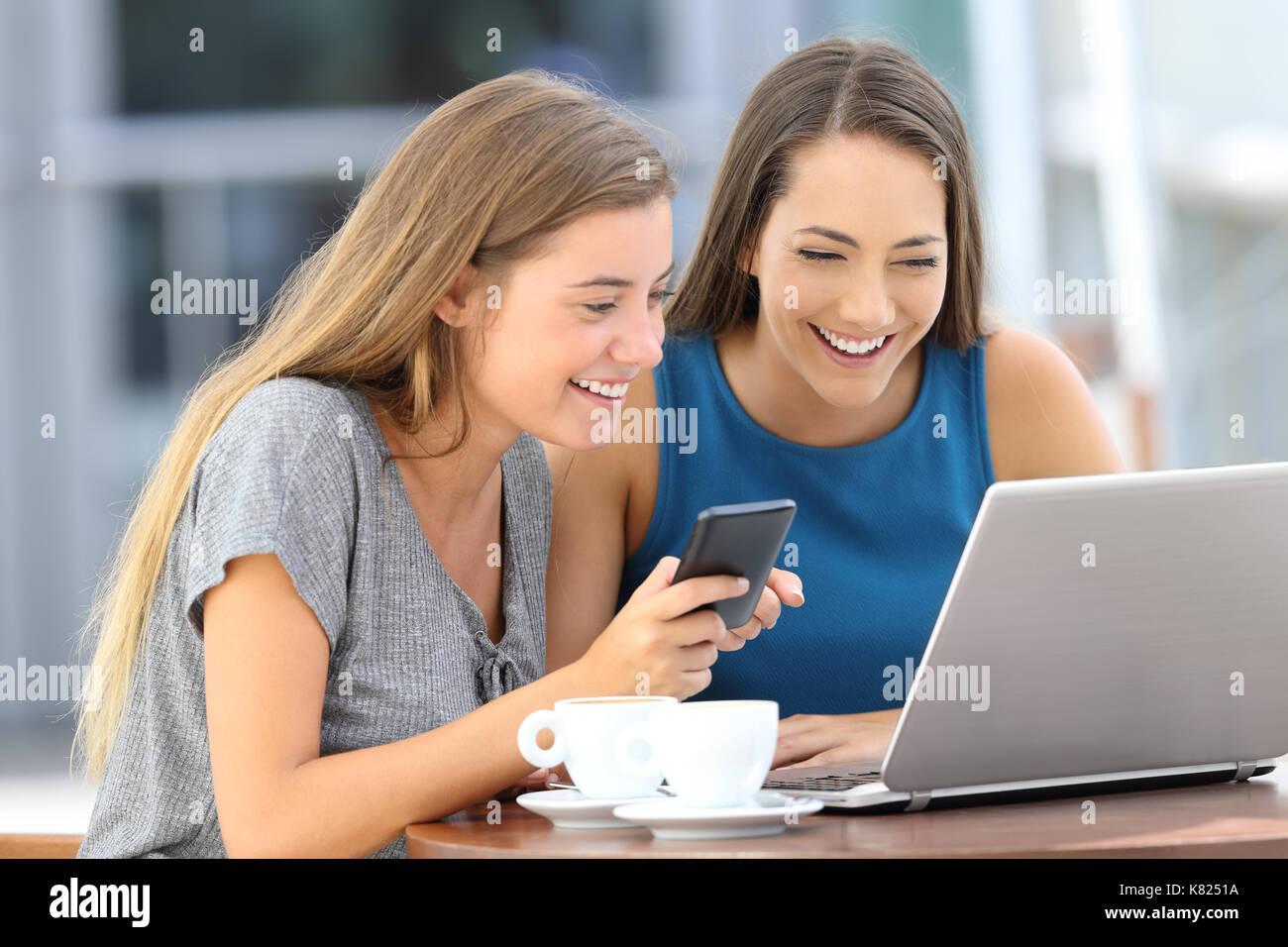 Due happy amici usando un portatile e un telefono intelligente seduto in un bar terrazza Immagini Stock