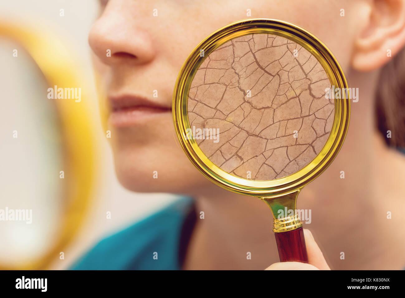 Invecchiamento e asciugare la pelle del viso concetto - donna con lente di ingrandimento Immagini Stock