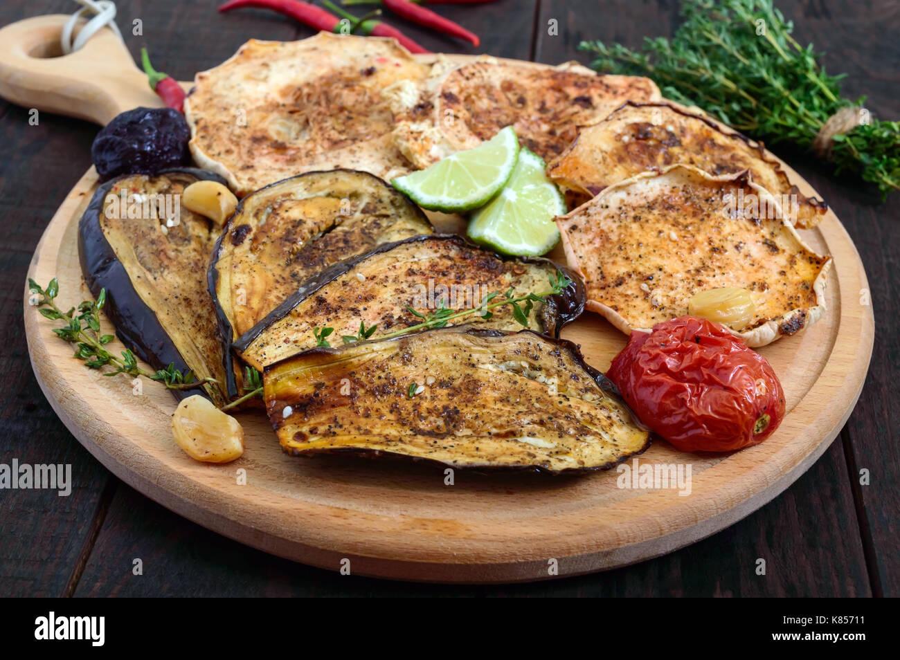 Verdure al forno: melanzane, patisson, pomodori in un giro di supporto di legno su uno sfondo scuro. piatto vegano. Foto Stock