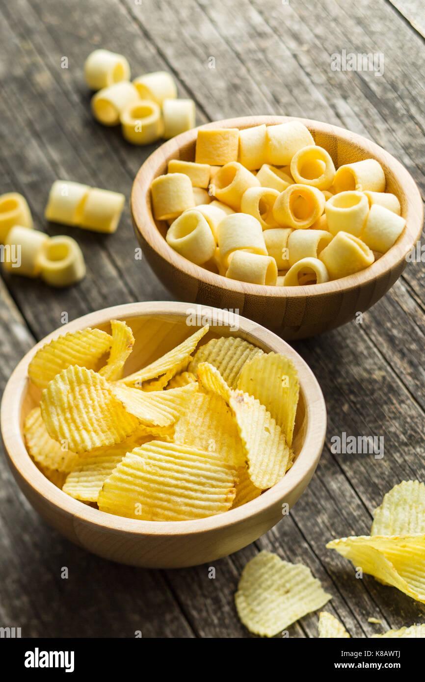 Croccanti patatine e gli anelli nel recipiente. Salate potato chips. Immagini Stock