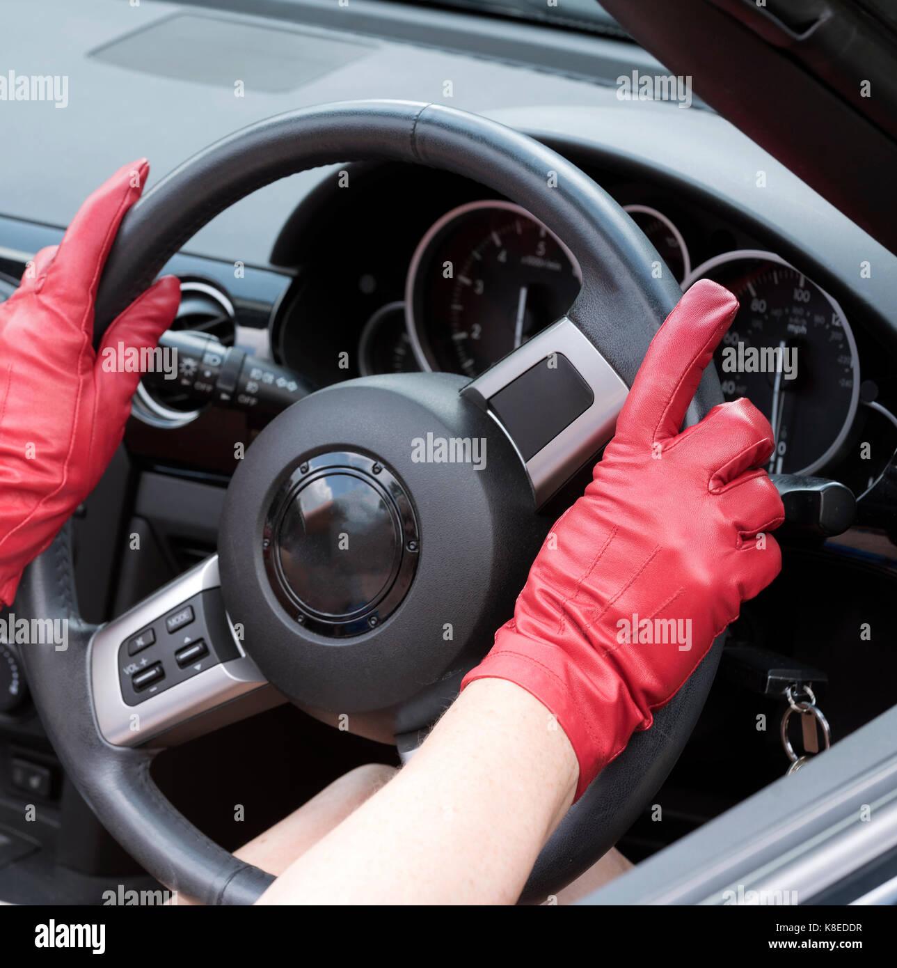 Rosso guanti in pelle tenendo un volante di sterzo Immagini Stock