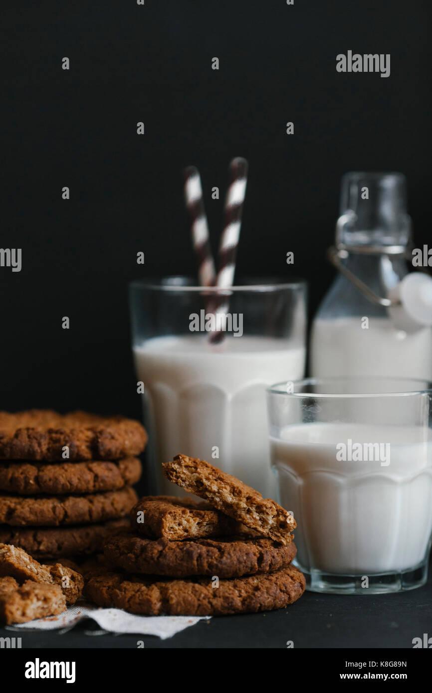 Biscotti e latte sulla tavola su sfondo nero Foto Stock