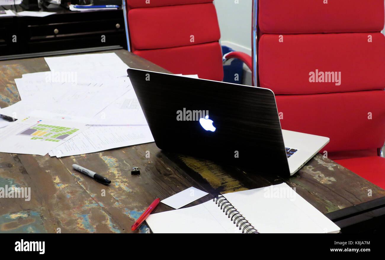 Rosso di due sedie per ufficio seduti ad un tavolo con un mac book