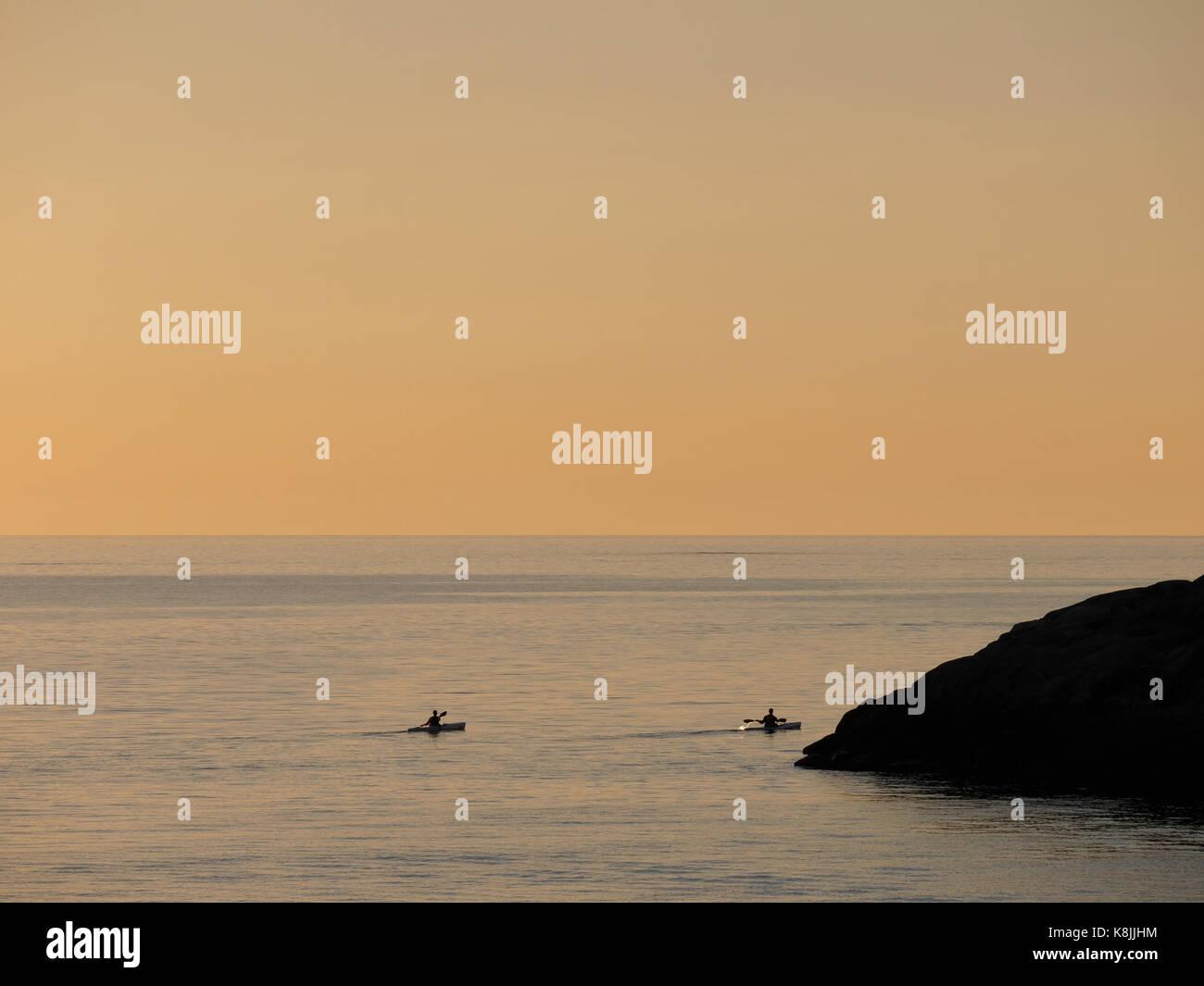 Due persone in kayak al tramonto fuori Klåva, Hönö, l'arcipelago di Goteborg, Svezia. Foto Stock