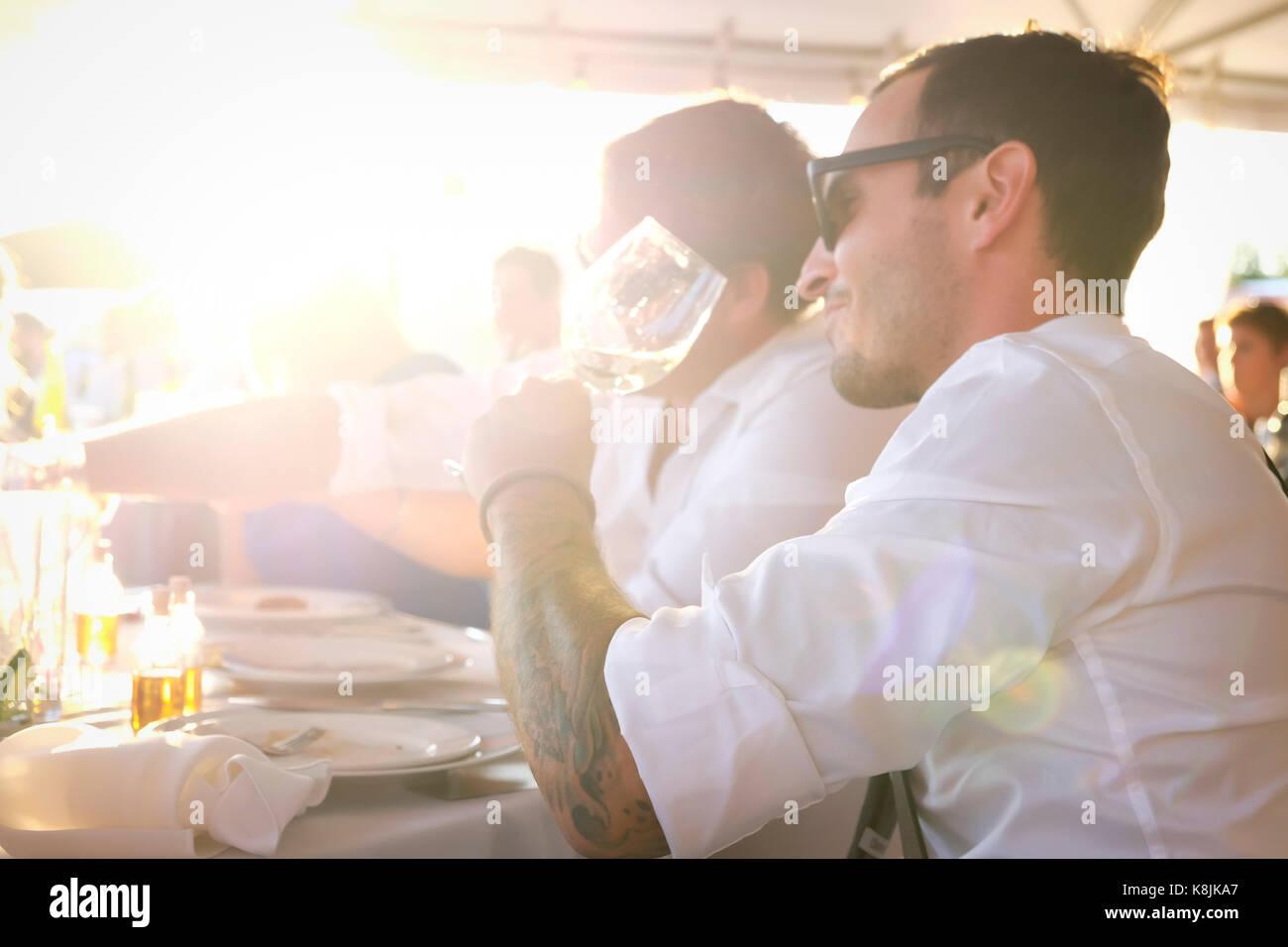 Colpo all'aperto del bel giovane uomo beve il vino a una festa estiva con un amico Foto Stock