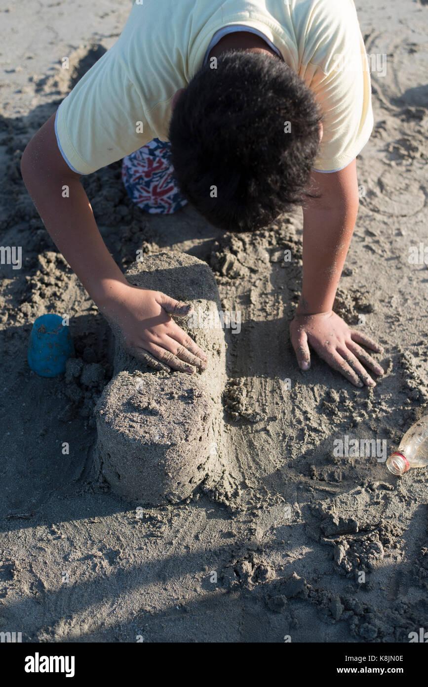 Il ragazzo sta facendo un castello di sabbia sulla spiaggia la sera Immagini Stock