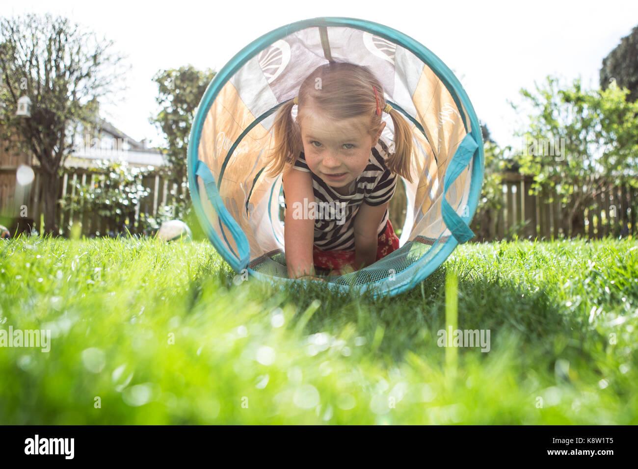 Bambina giocare in giardino Immagini Stock