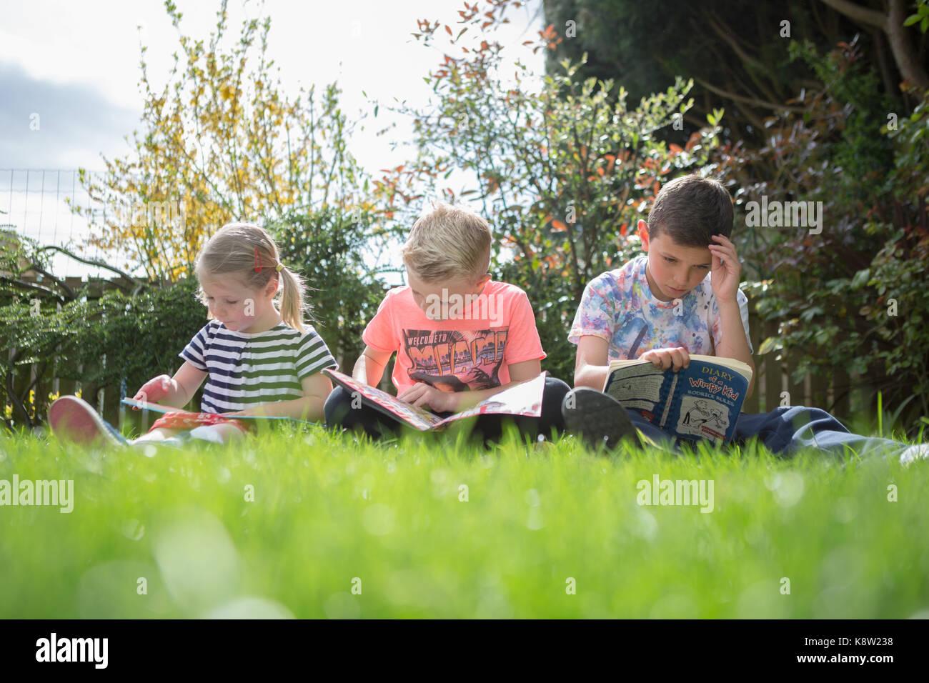 Lettura per bambini in giardino Immagini Stock