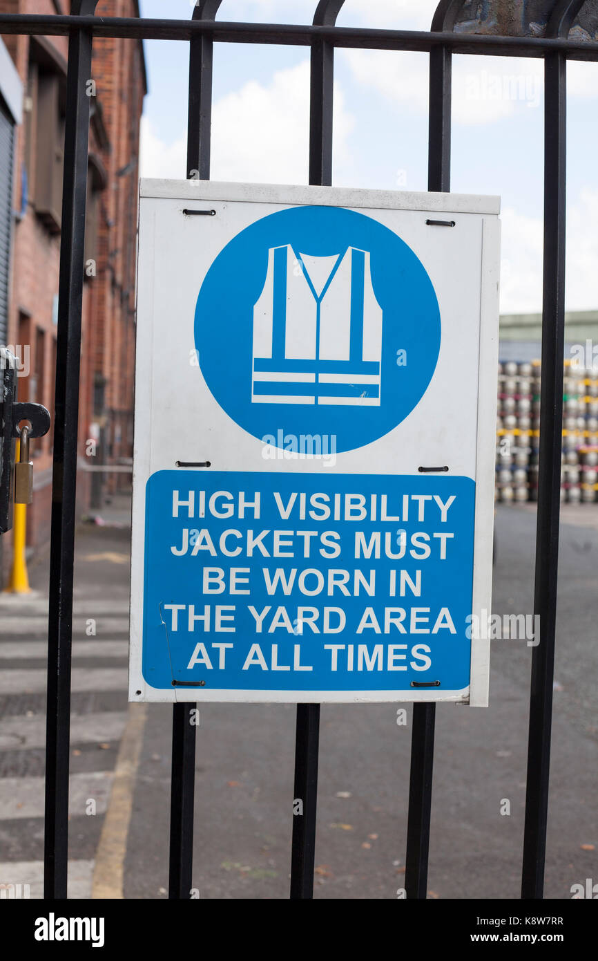 Un segno su in società di produzione ad alta visibilità giacca deve Immagini Stock