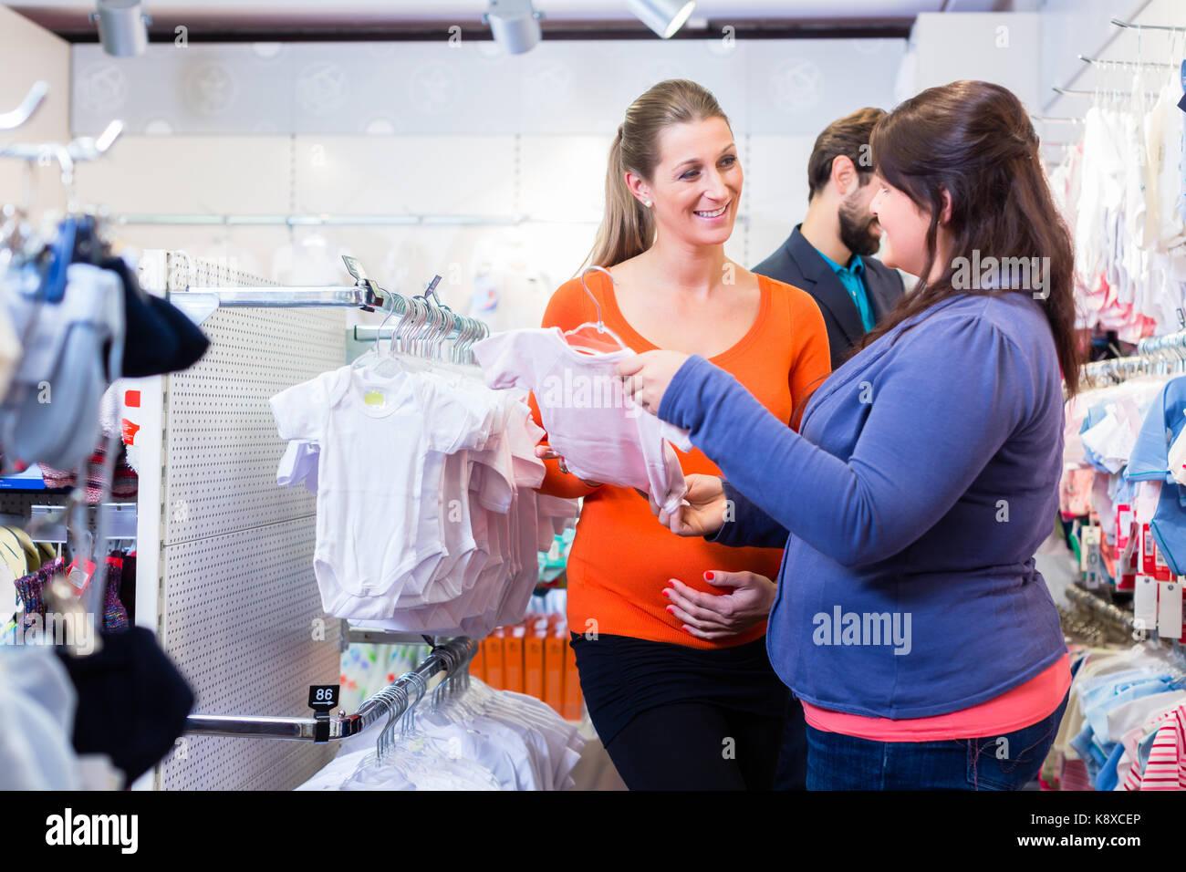 Addetto alle vendite con coppia comprare vestiti del bambino in negozio c4f7e743c7d