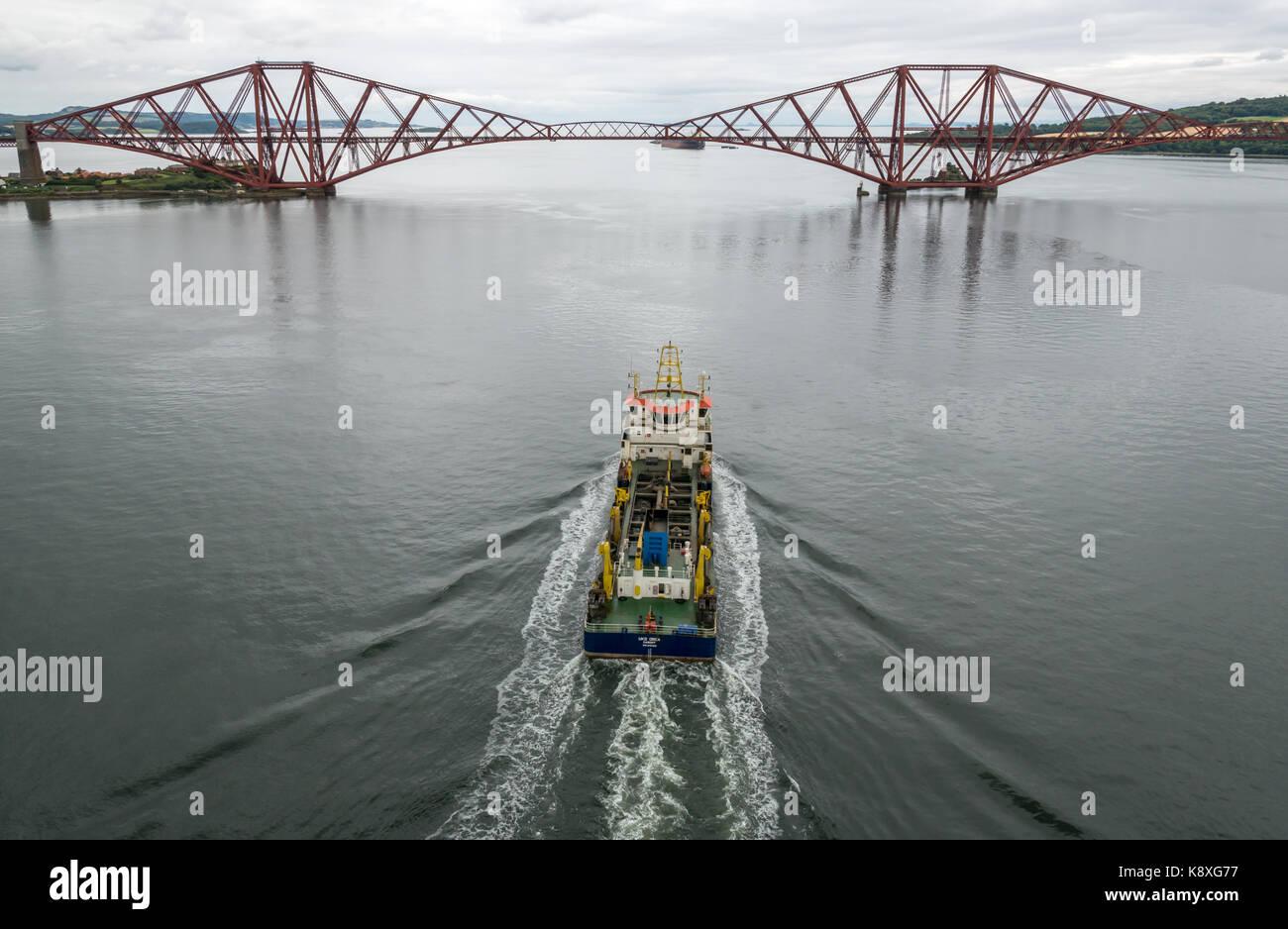 UKD Orca, una tramoggia di aspirazione draga a vela a sbalzo verso il Ponte di Forth Rail in acque calme, Firth Immagini Stock