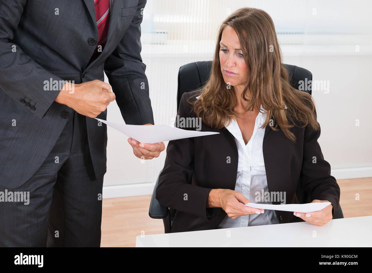 Close-up di imprenditore che mostra documento al dipendente di sesso femminile in office Immagini Stock